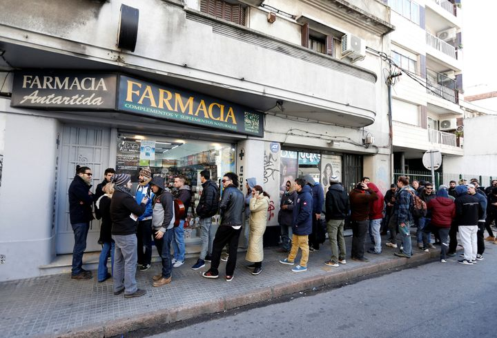 People queue in line outside of a pharmacy to buy legal marijuana in Montevideo, Uruguay July 19, 2017.
