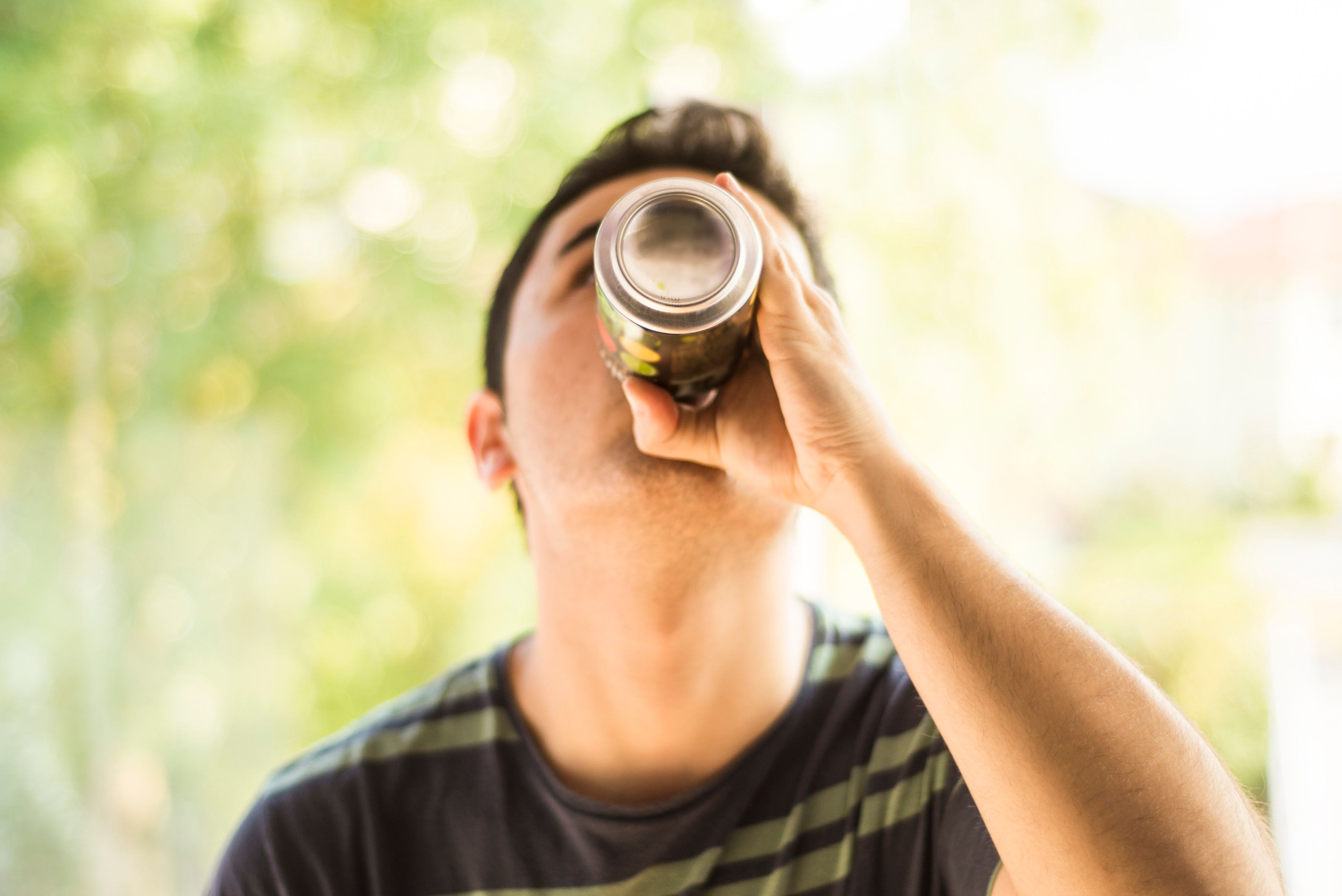 A young man drinking a can.