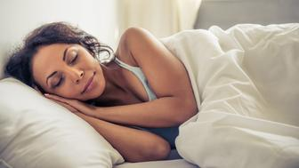 Side view of beautiful young Afro American woman smiling while sleeping in her bed at home