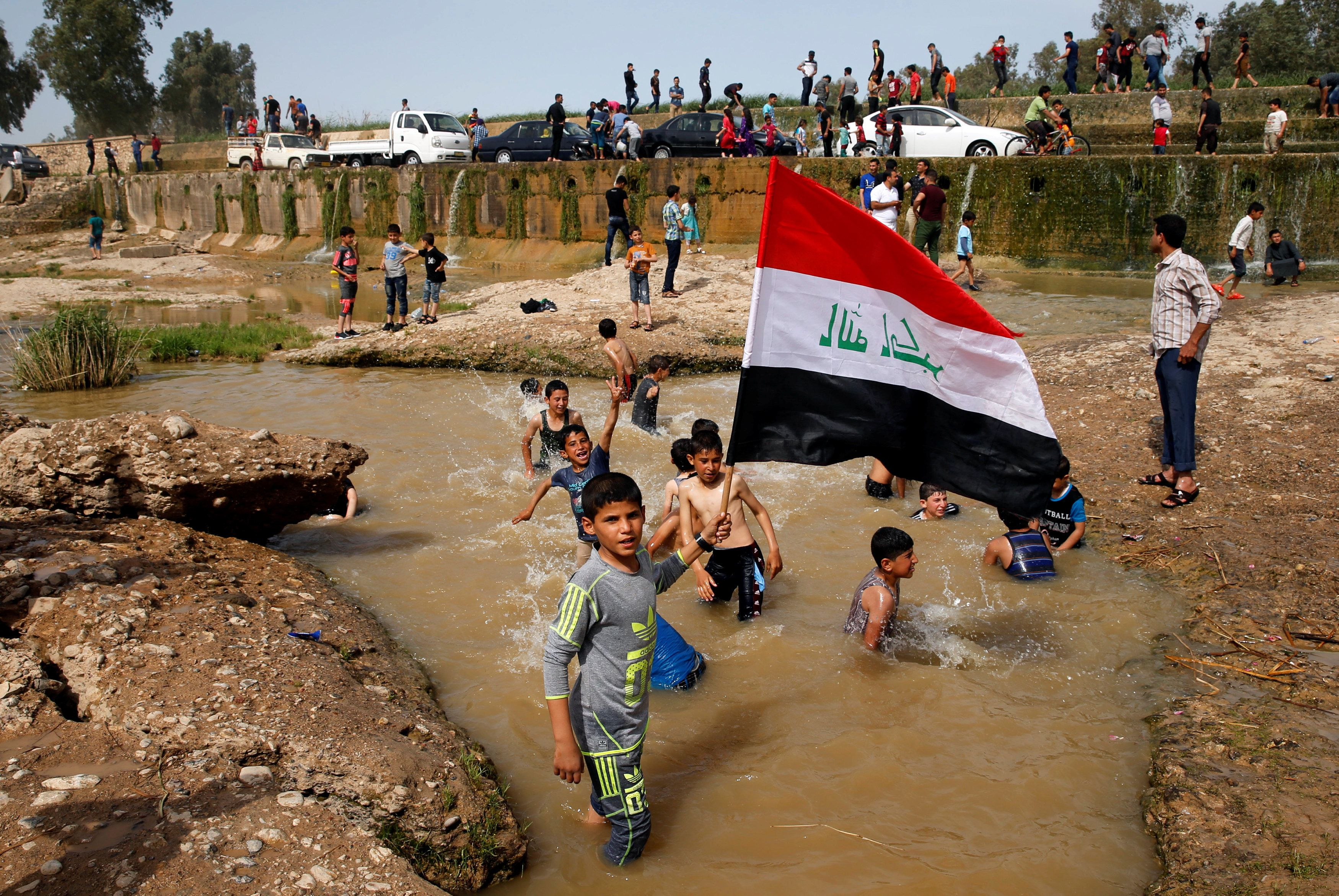 "A boy holds the Iraqi flag as he plays in the water with other children during a Friday holiday at Shallalat district (Arabic for ""waterfalls"") in eastern Mosul, Iraq, April 21, 2017. REUTERS/Muhammad Hamed     TPX IMAGES OF THE DAY"