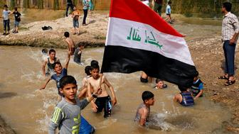 """A boy holds the Iraqi flag as he plays in the water with other children during a Friday holiday at Shallalat district (Arabic for """"waterfalls"""") in eastern Mosul, Iraq, April 21, 2017. REUTERS/Muhammad Hamed     TPX IMAGES OF THE DAY"""