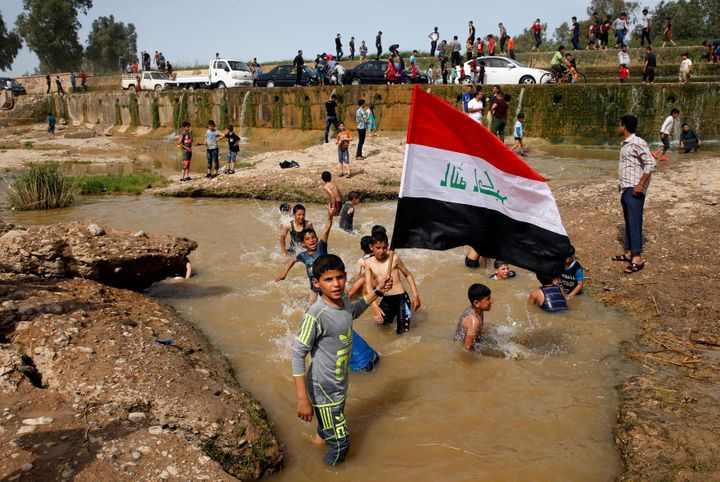 A boy holds the Iraqi flag as he plays in the water with other children during a Friday holiday in the Shallalat district of