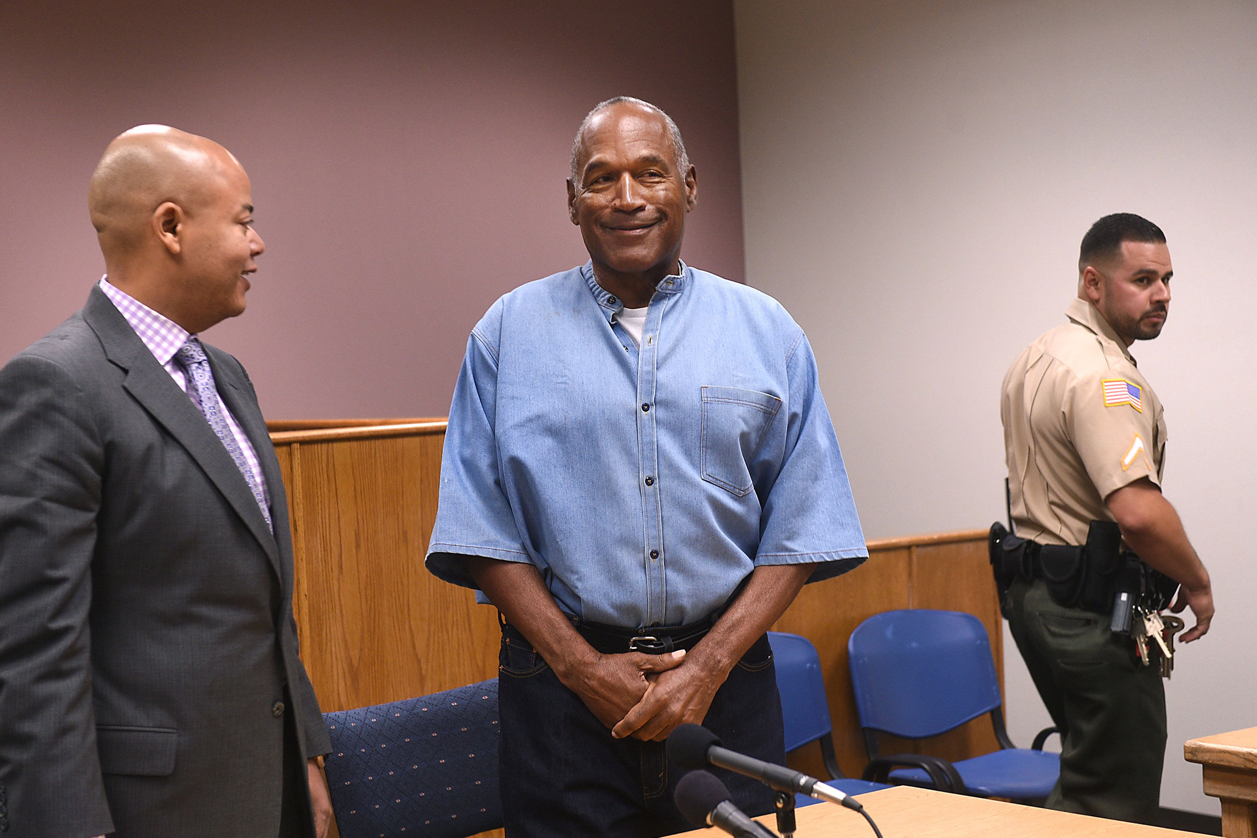 Former professional football player O.J. Simpson, center, stands during a parole hearing at Lovelock Correctional Center in Lovelock, Nevada, U.S., on Thursday, July 20, 2017. Simpson may learn, as early as Thursday afternoon, whether the Nevada Board of Parole Commissioners will decide to free him in the fall or whether he will continue to serve a nine-to-33-year sentence for 12 convictions, including kidnapping and armed robbery, stemming from a 2007 sting operation in which he tried to recover sports memorabilia from two collectors. Photographer: Jason Bean/Pool via Bloomberg