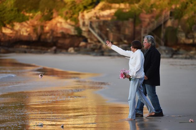 The parents of Justine Damond, John Ruszczyk and Maryan Heffernan, throw a flower into the water during...