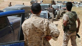 Armed men stand guard as a convoy of Syrian refugees leaves the Lebanese eastern border town of Arsal heading towards the Syrian region of Qalamoun on July 12, 2017 as part of a deal that was negotiated by Syrian rebels in the camps and Lebanon's Hezbollah group. Around 300 Syrian refugees returned from camps near a restive border town in northeast Lebanon to their Syrian hometown, a security source and AFP correspondent said. / AFP PHOTO / STRINGER        (Photo credit should read STRINGER/AFP/Getty Images)