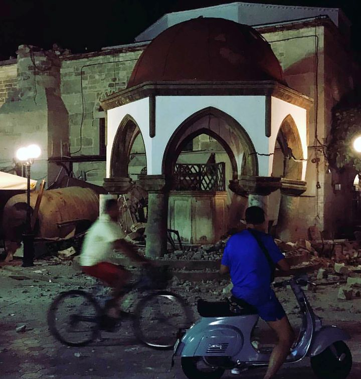 People pass by damaged buildings after an earthquake on the Greek island of Kos early Friday.