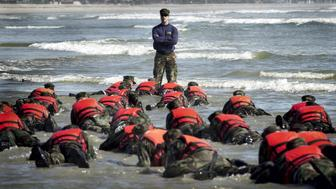 CORONADO, CA - APRIL 15:  During a Hell Week surf drill evolution, a Navy SEAL instructor assists students from Basic Underwater Demolition/SEAL (BUD/S) class 245 with learning the importance of listening April 15, 2003 in Coronado, California. The intense physical and mental conditioning it takes to become a SEAL begins at BUD/S training. During this six-month mind and body obstacle course, recruits are pushed to their physical and mental limits. Further development of the core values, Honor, Courage, Commitment and Integrity, is an essential component of SEAL training and one that is weaved throughout a SEAL's career. First phase is the basic conditioning phase and is eight weeks in length. Physical training involves running, swimming, and calisthenics, all of which become increasingly difficult as the weeks progress. The fourth week of training, 'Hell Week,' is five-and-a-half days of continuous training with very little sleep. This week is designed to push students to their maximum capability both physically and mentally. The remaining weeks are spent in hydrographic reconnaissance and basic maritime training.  (Photo by Photographer's Mate 2nd Class Eric S. Logsdon/U.S. Navy via Getty Images)