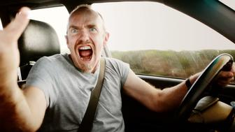 An angry man glares through his passenger-side window, gesturing and yelling in a fit of road rage.