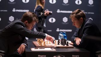 World Champion Magnus Carlsen makes a move against challenger Sergey Karjakin