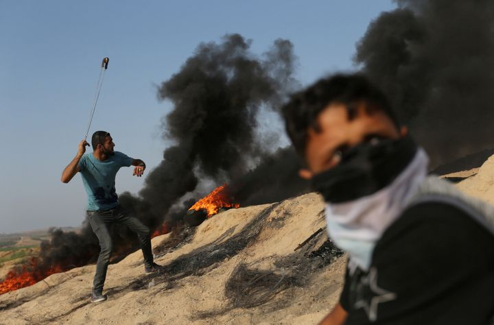 A Palestinian protester uses a sling to hurl stones towards Israeli troops during clashes near the border between Israel and