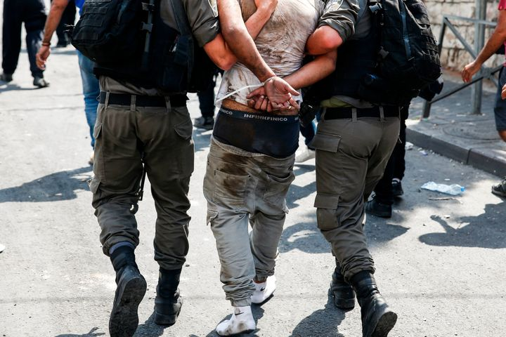 Israeli security forces detain a Palestinian protester during clashes following prayers outside Jerusalem's Old City on July