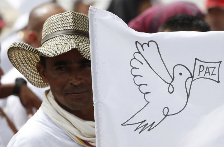 A FARC member waves a white peace flag to commemorate the completion of their disarmament.