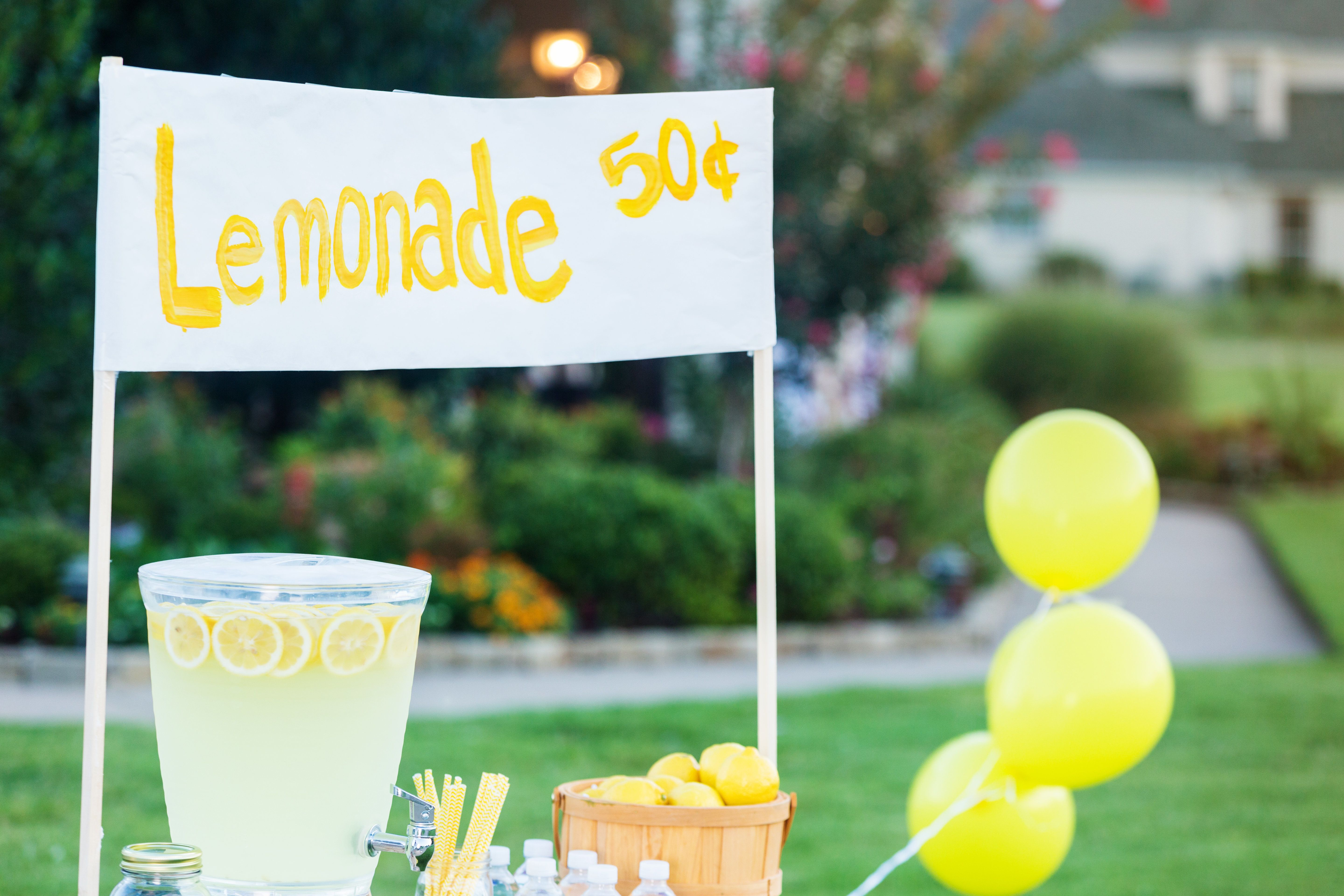 A lemonade stand is set up in the front yard of a home in the suburbs. A beverage dispenser and a basket of fresh lemons are on the stand. A sign is at the top of the stand with the price of the lemonade.