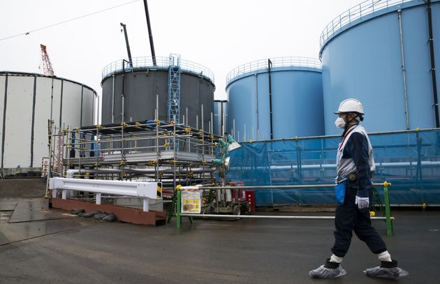 An employee walks past storage tanks for contaminated water at the Tokyo Electric Power Co.'s Fukushima...