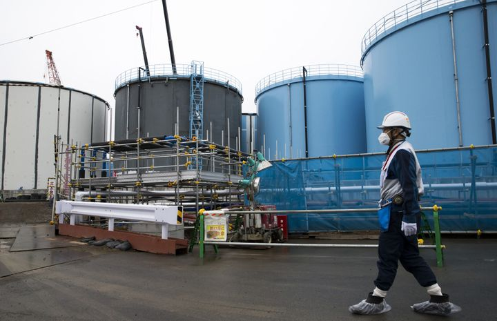 An employee walks past storage tanks for contaminated water at the Tokyo Electric Power Co.'s Fukushima Dai-ichi nuclear powe