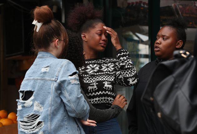 People react outside a shop in Kingsland Road, east