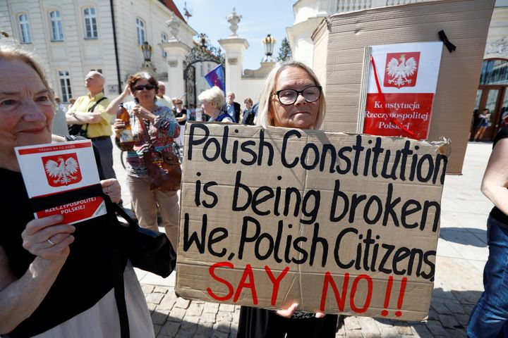 People gather in front of the Presidential Palace during a Sunday protest against the Supreme Court legislation in Warsaw, Po