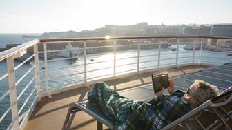 Woman relaxes with digital tablet under blanket near railing of ship, Mediterranean cruise