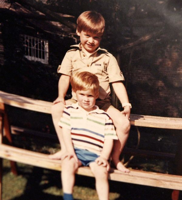 Prince William and Prince Harry sit together on a picnic bench.