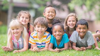 A multi-ethnic group of elementary age children are lying in a row in the grass and are smiling while looking at the camera.