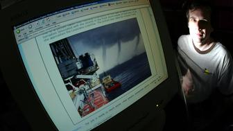 David Mikkelson next to his computer monitor with a doctored storm photo in which two extra tornados were added to the original which had only one. David 44, and Barbara Mikkelson 45, of Agoura Hills run a website called www.snopes.com which is dedicated to urban legends and separating fact from fiction in rumors, gossip, and stories circulating on the Internet and by word of mouth.  (Photo by Stephen Osman/Los Angeles Times via Getty Images)