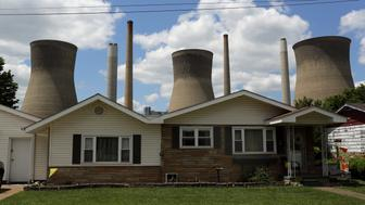The John Amos coal-fired power plant is seen behind a home in Poca, West Virginia May 18, 2014. With coal production slowing due to stricter environmental controls, the availability of natural gas and a shift to surface mining, the state's coal country has been hit hard with job losses and business closures. Picture taken May 18, 2014.    REUTERS/Robert Galbraith  (UNITED STATES - Tags: BUSINESS COMMODITIES ENERGY EMPLOYMENT SOCIETY)   ATTENTION EDITORS - PICTURE 18 OF 27 FOR WIDER IMAGE STORY 'DECLINE ALONG 'THE KING COAL HIGHWAY''  SEARCH 'GALBRAITH COAL' FOR ALL IMAGES