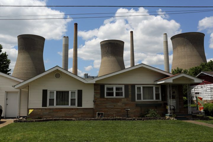 The John Amos coal-fired power plant rises behind a home in Poca, West Virginia, in 2014.