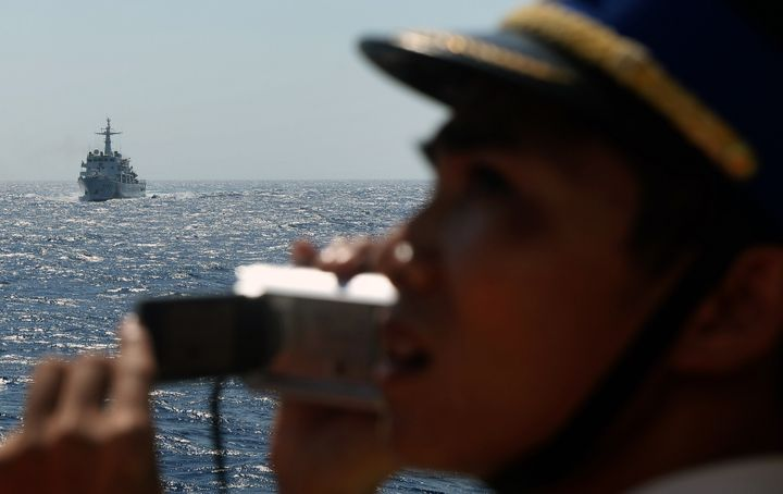 A Vietnamese Coast Guard officer takes a picture of a Chinese Coast Guard ship near Vietnam's central coast. M