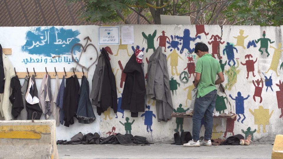 A man in Beirut leaves clothes at the wall of