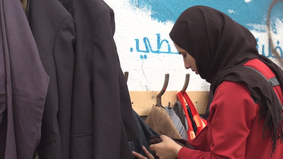 A lady looks at some clothes at the 'wall of