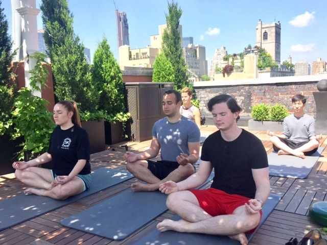 The GlassView team meditates together on the rooftop of their New York office.
