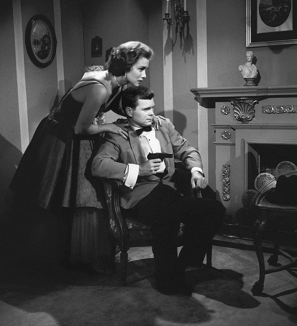American actor Barry Nelson sits in a chair and aims a gun at an unseen assailant as actress Linda Christian (as Valerie Math