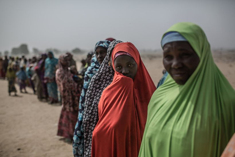 Aisatu with a group of women at the entrance to the displaced people's camp of Muna Garage on the outskirts of Maiduguri, Nig