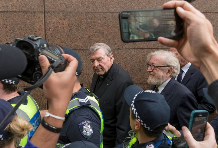 George Pell is surrounded by Australian police and members of the media as he leaves the Melbourne Magistrates Court.