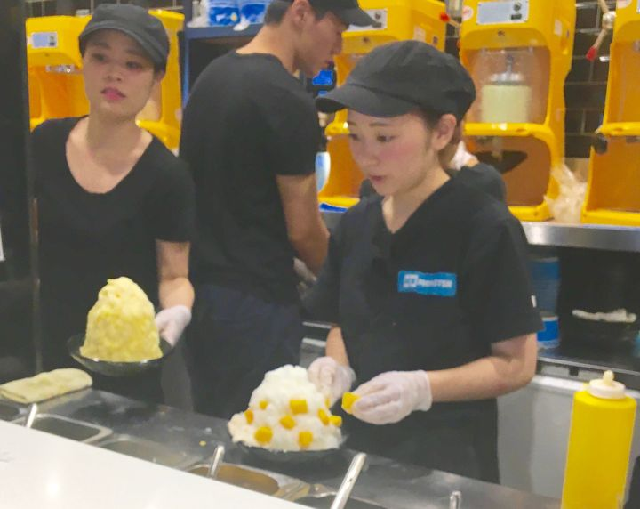 Staff at Ice Monster Kaki Kori creamery put the finishing touches on towers of shaved ice.