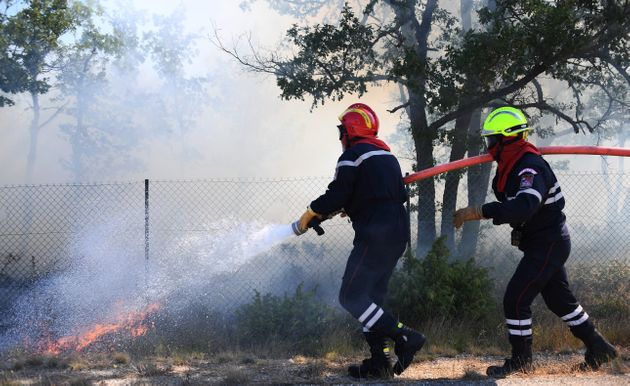 <strong>Firefighters try to extinguish a fire burning in Artigues, southeastern