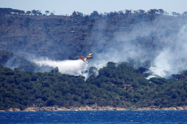 <strong>A firefighting plane drops water to extinguish a forest fire on La