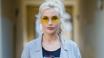 WARSAW, POLAND - MARCH 31: Portrait of Singer and model Karolina Gilon wearing coat Malgorzata Salamon ,top vintage band shirt Kiss, belt vintage, denim jeans H&M, boots Halens, earrings Zozo Design, sunglasses Ray-Ban, bag Pinko on March 31, 2017 in Warsaw, Poland. (Photo by Christian Vierig/Getty Images)