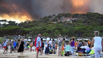 People leave the beach with their belongings as they look at fire burning a forest behind them in Bormes-les-Mimosas, southeastern France, on July 26, 2017. At least 10,000 people, including thousands of holidaymakers, were evacuated overnight after a new wildfire broke out in southern France, which was already battling massive blazes, authorities said on July 26. / AFP PHOTO / Anne-Christine POUJOULAT        (Photo credit should read ANNE-CHRISTINE POUJOULAT/AFP/Getty Images)
