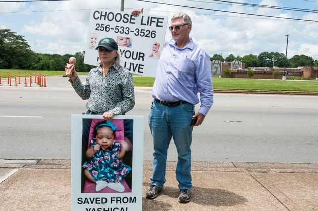 Anti-abortion protesters outside a clinic in Huntsville, Alabama, hold signs featuring a child they claim...