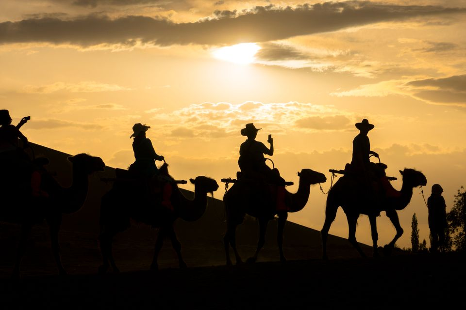 Tourists ridecamels in the Mingsha Shan desert, part of the ancient Silk Roads, during the Silk...