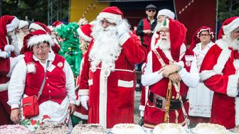 People dressed as Santa Claus stand in front of cakes as they take part in the World Santa Claus Congress, an annual event held every summer at the amusement park Dyrehavsbakken, in Copenhagen, Denmark. Scanpix Denmark/Sarah Christine Noergaard/via REUTERS    ATTENTION EDITORS - THIS IMAGE WAS PROVIDED BY A THIRD PARTY. DENMARK OUT. NO COMMERCIAL OR EDITORIAL SALES IN DENMARK. NO COMMERCIAL SALES.