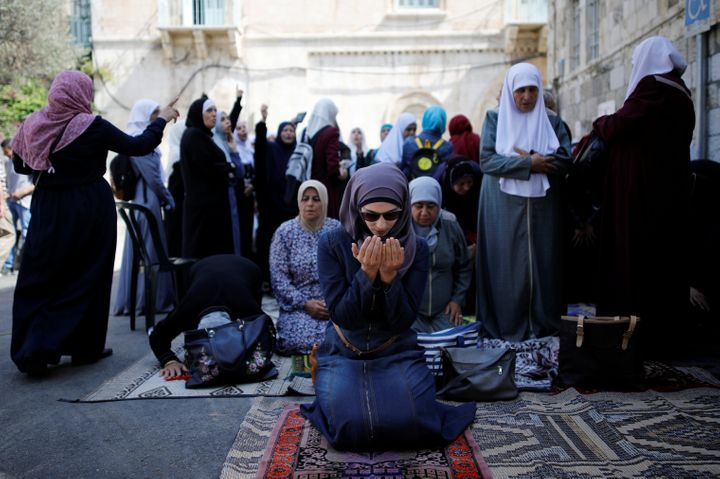 Palestinian women pray as others shout slogans outside the compound known to Muslims as Noble Sanctuary and to Jews as Temple