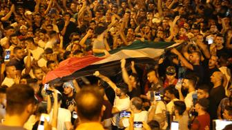 JERUSALEM - JULY 26: Palestinians celebrate in front of the Lion's Gate entrance to Al Aqsa mosque after more Israeli iron guardrails were removed from the Al-Aqsa Compound in Jerusalem, on July 26, 2017. While Palestinians immediately celebrated the removal at the Esbat Gate of Al-Aqsa some remained cautious.  (Photo by Mostafa Alkharouf/Anadolu Agency/Getty Images)