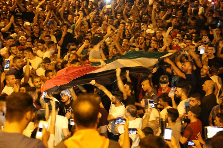 Palestinians celebrate in front of the Lion's Gate entrance to Al Aqsa mosque after more Israeli iron guardrails were removed
