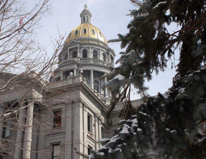 The dome of the Colorado Statehouse is framed between trees.