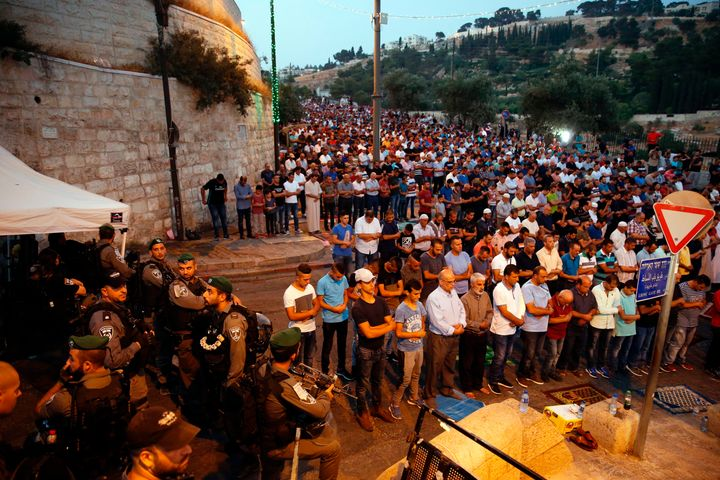 Israeli security forces stand by as Palestinian Muslim worshippers pray outside Lions' Gate, a main entrance to the Al-Aqsa m