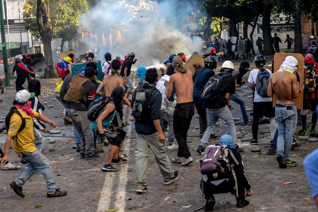 Opposition demonstrators skirmish with riot police after an anti-government protest in Caracas, Venezuela,...