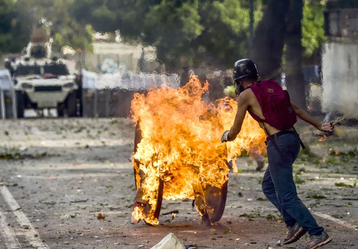An opposition demonstrator pushes a wooden reel set ablaze toward a line of riot police during clashes in Caracas, Venezuela,