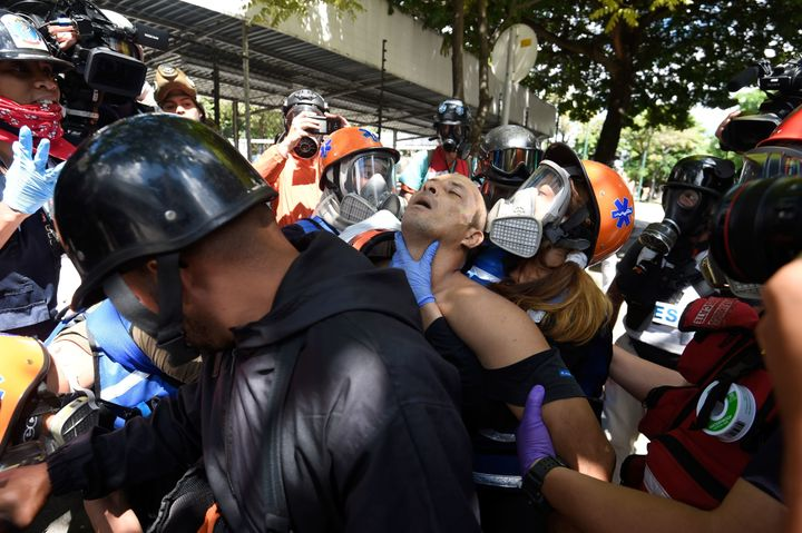 An anti-government activist is assisted and carried away on a motorbike during the opposition's48-hour general strike i